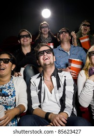 Happy people at the movie theater wearing 3d glasses