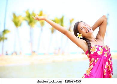 Happy people on beach travel - woman in sarong cheerful in happiness during summer vacation holidays on Hawaii. Multiracial Caucasian / Asian female girl.