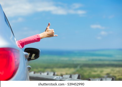 Happy people on the road. Hand making a hang loose sign out a car window.