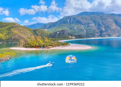 Happy people parasailing on Oludeniz Beach in summer - Fethiye, Turkey