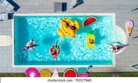 Happy people partying in an exclusive swimming pool with animal and fruit shapes mats, view from above