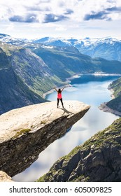Happy people relax in cliff during trip Norway. Trolltunga hiking route
