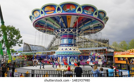 Happy people ride the carousel through the sky.  Sea to Sky Swinger, Playland Vancouver's favourite amusement park. August 16. 2019. Vancouver, BC, Canada.