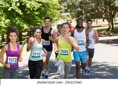 Happy people running race in park on a sunny day