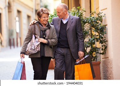 Happy people with senior man and woman shopping and walking with bags in italian city street