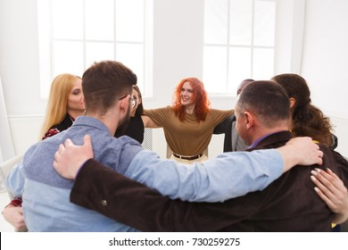 Happy people sitting in circle, hugging each other. Meeting of support group, copy space. Teambuilding concept