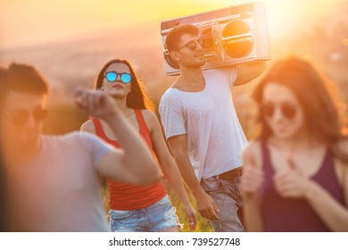 The happy people stand with a boom box on the bright sun background