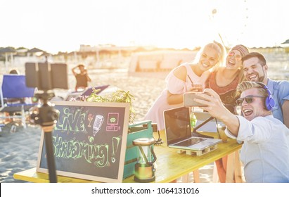 Happy people taking selfie and video feed from beach party at sunset - Man vlogger using mobile phone camera for filming streaming live - New technology trends concept - Focus on blond guy face