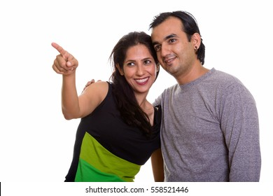 Happy Persian couple smiling and looking at distance together with woman pointing finger isolated against white background