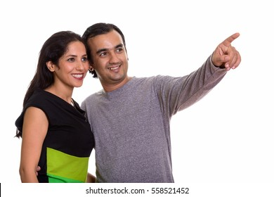 Happy Persian couple smiling and looking at distance together with man pointing finger isolated against white background