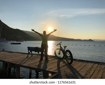 Happy person with bike and sunrise on the sea