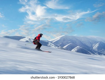 Happy person in red jacket skiing down slope in bright sunshine on blue sky, with high snow covered mountains in background. Blurred motion.