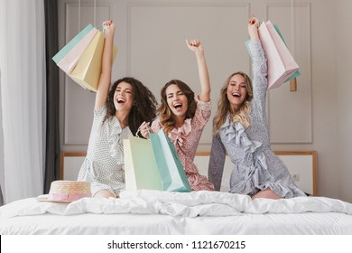 Happy photo of lovely smiling women 20s wearing dresses rejoicing and screaming with colorful shopping bags in hands while sitting on cozy bed in hotel room during hen party