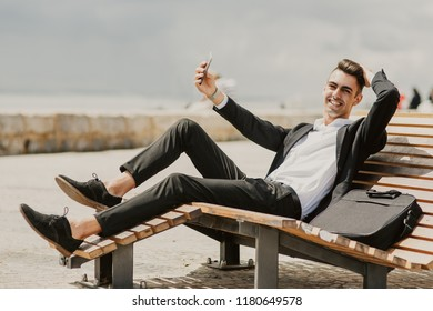 Happy photogenic male manager posing for selfie while relaxing on comfortable bench. Jolly handsome young businessman using smartphone to make video call while being on vacation. Technology concept