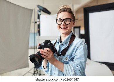 Happy photographer in modern photo-studio