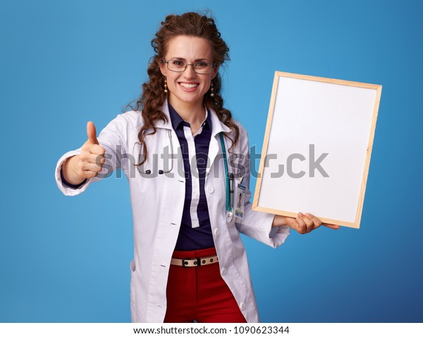 happy physician woman in white medical robe showing thumbs up and and blank board isolated on blue
