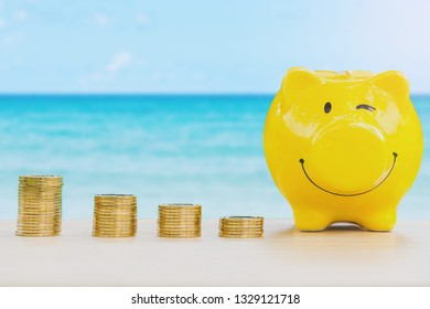 happy piggy bank and coins stack over blurred summer blue sea background, saving money concept.