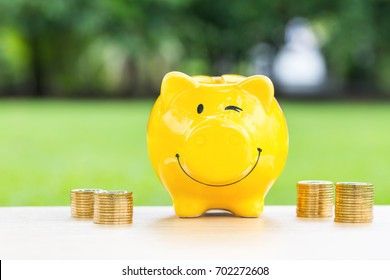 happy piggy bank and coins stack over blurred green garden  background, saving money concept.