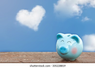 happy piggy bank on wooden floor over blue and cloudy sky background.