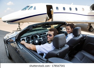 Happy pilot and airhostess in convertible against private jet at terminal