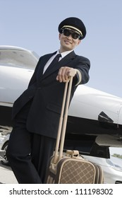 Happy pilot standing with luggage and airplane in the background at airfield