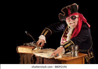 Happy pirate sits at a table with book, quill pen, musket, mug, and torn treasure map. He is wearing a nineteenth century pirate costume with jeweled eye patch. Dark background with copy space.
