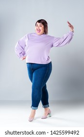 Happy pize size model in casual clothes, fat woman on gray studio background, body positive concept