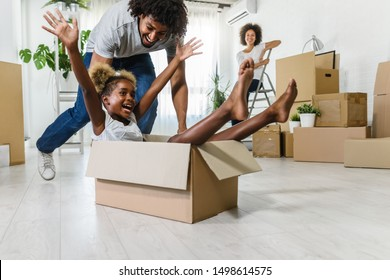 Happy playful  African American family moving in new apartment, little preschooler daughter sitting in cardboard boxes, father rolling her,  purchase property concept