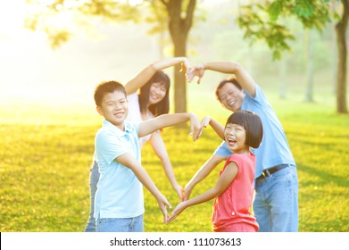 Happy playful Asian family forming love shape, outdoor green park