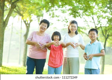 Happy playful Asian family forming love shape at outdoor green park