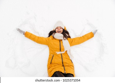 Happy playful brunette lady lying on snow and making snow angel figure with hands and legs
