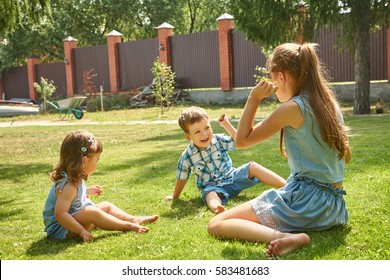 happy playful children outdoors in the summer on the grass in a backyard
