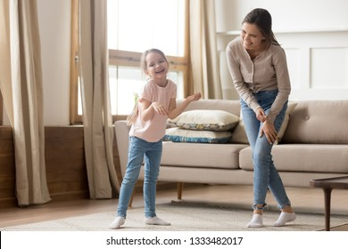 Happy playful cute child daughter laughing enjoy funny home activity with young mom, elder sister or baby sitter, funny little kid girl and cheerful mother having fun dancing together in living room