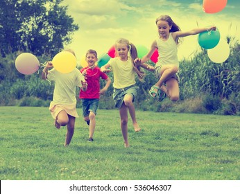 happy playful elementary school age boy and girls with air balloons in hands running in summer park. Selective focus