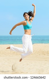 Happy playful girl jumping and dancing fun on summer holidays beach. Caucasian sporty beautiful woman.