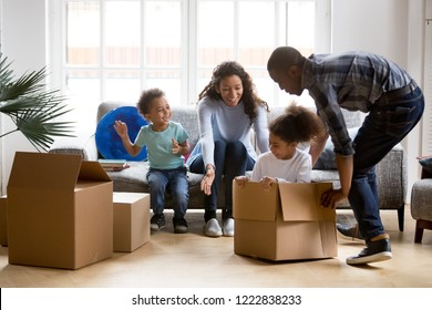 Happy playful large African American family moving in new apartment, little preschooler daughter sitting in cardboard boxes, father rolling her to mother, playing together, purchase property concept