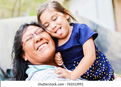 Happy playful latin mom with little daughter.