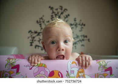 happy playful suprised baby peeking out of a playpen