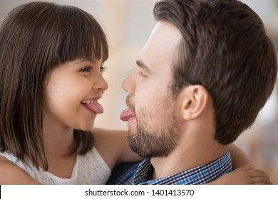 Happy playful young dad and little daughter have fun together feel childish show tongues, smiling father and preschooler kid enjoy playing funny game, hug spending time at home. Parenthood concept