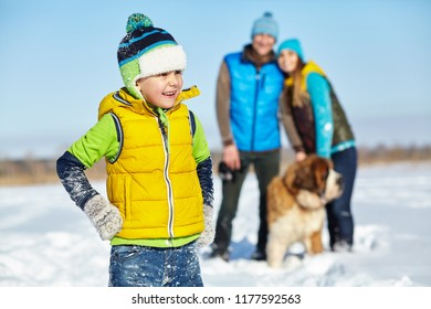 happy playing family with St. Bernard dog in the winter. active people outdoors