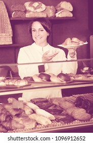 Happy pleasant female cooks demonstrating and selling to the customer pastry in the cafe counter