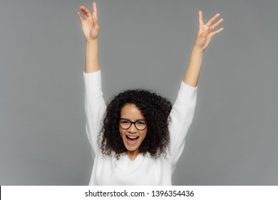 Happy pleased young woman raises hands up, being in high spirit, dances over grey background, celebrates someting, has Afro haircut, wears white jumper, transparent glasses for vision correction
