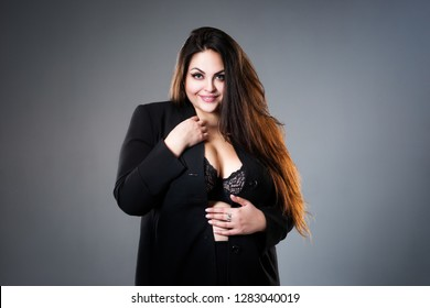 Happy plus size fashion model in sexy clothes, fat woman on gray studio background, overweight female body