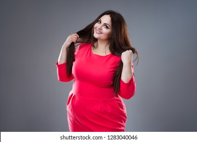 Happy plus size fashion model in red dress, sexy fat woman on gray studio background