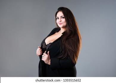 Happy plus size fashion model in sexy clothes, fat woman on gray studio background, body positive concept, studio shot