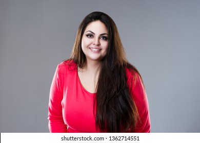 Happy plus size fashion model in red dress, sexy fat woman on gray studio background, body positive concept