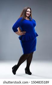 Happy plus size fashion model in blue dress, fat woman on gray studio background, body positive concept, full length portrait