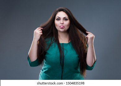 Happy plus size fashion model in green dress, fat woman shows tongue on gray studio background, body positive concept