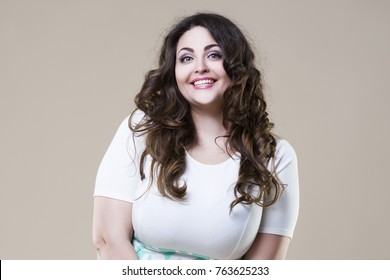 Happy plus size fashion model in casual clothes, sexy fat woman on beige studio background