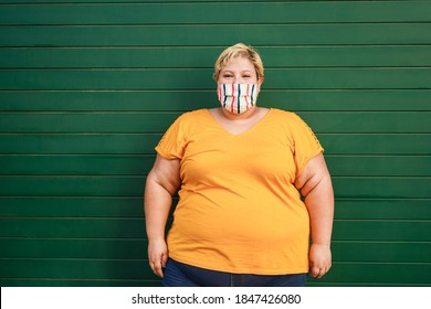 Happy plus size woman wearing a face protective mask during coronavirus outbreak - Focus on face